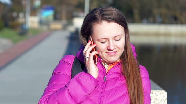 Beautiful young girl in park, on lake, talking on phone. Pink clothes, springtime, Slow motion, close up shot video