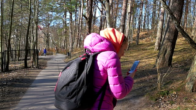 Beautiful Young Girl in Woods looks phone maps and touches hair. Pink clothes, spring forest, Slow motion video