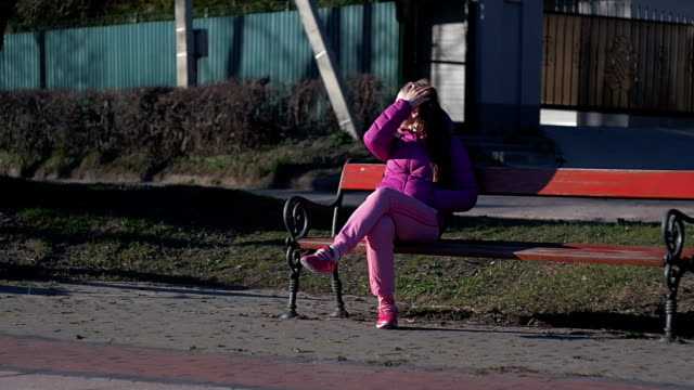 Beautiful young girl is sitting on bench. Pink clothes, spring time, Slow motion. Full shot video