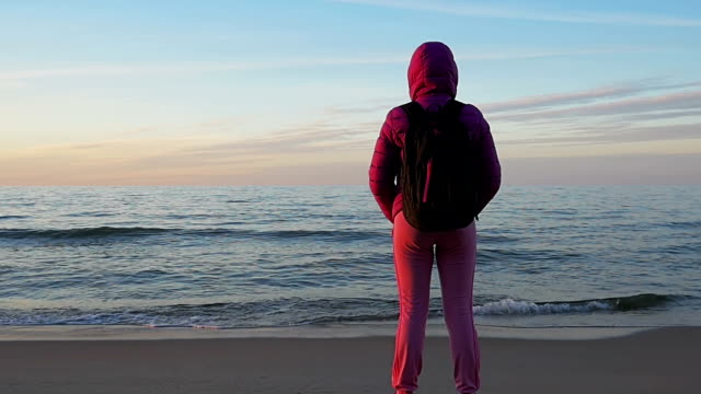 Beautiful young girl looks at calm sea and blue sky. Relaxation. Pink clothes, spring time, Slow motion. Medium Shot video