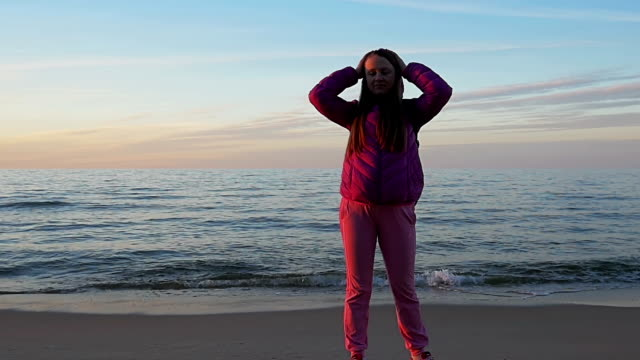 Beautiful young girl looks at camera on background of calm sea and blue sky. Smiles and takes off hood of jacket. Pink clothes, spring time, Slow motion. Medium Shot video