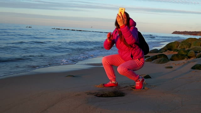 Beautiful young girl on beach doing selfie on phone. Pink clothes, spring time, Slow motion. Medium Shot video