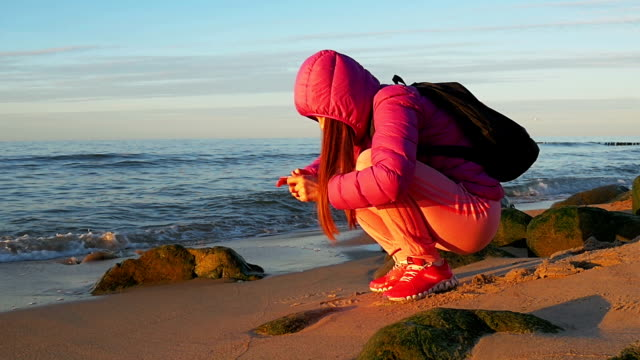 Beautiful young girl on beach, makes photo on phone Pink clothes, spring time, Slow motion. Medium Shot video