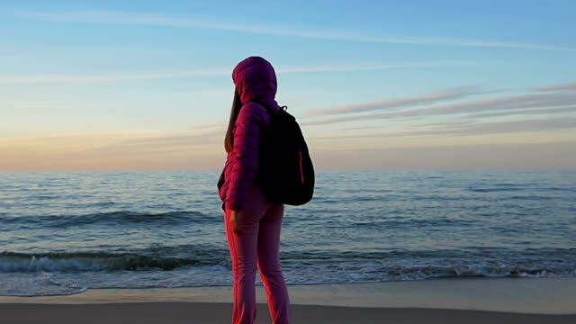 Beautiful young girl talking on phone on background calm sea and blue sky. Pink clothes, spring time, Slow motion. Medium Shot video