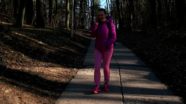 Beautiful young girl walking in forest and talking phone. Pink clothes, spring forest, Slow motion video