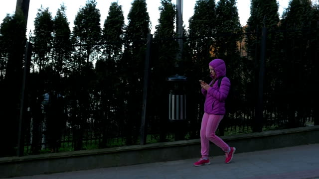 Beautiful young girl walking in shade of a tree, walking down a hill on background of iron fence with trees. Pink clothes, spring time, Slow motion. Full shot video