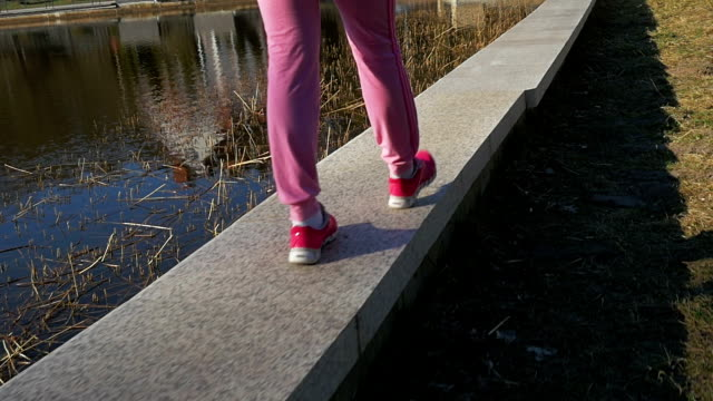 Beautiful young girl walking stone parapet lake shore, evening. Legs, Pink clothes, springtime, Slow movement video