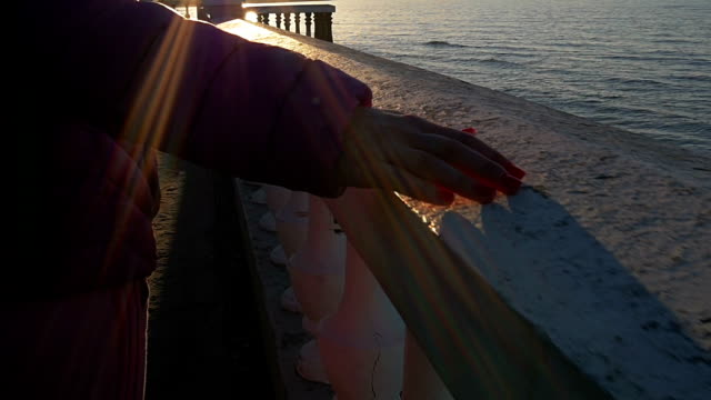 A beautiful young girl walks, touches stone parapet to sea. Pink clothes, spring time, Slow motion. Close-up shot video