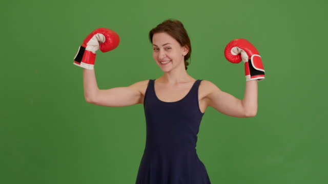 beautiful young girl with boxing gloves on a green screen. 4K video