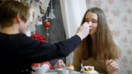 Beautiful young girl with brown hair sitting in a youth cafe with a teen man trying a delicious dessert with a spoon. Young boy feeds her video