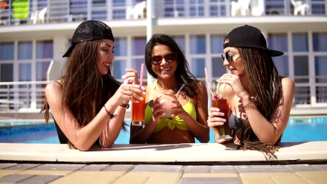Beautiful young girls in sunglasses drinking cocktails relaxing by the pool. Summertime pool party. Slowmotion shot video