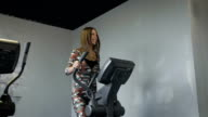 Beautiful young lady using the elliptical trainer in a gym in a positive mood video