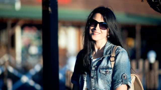 Beautiful young lady wearing stylish jeans jacket with long hair posing in cafe at sunset video