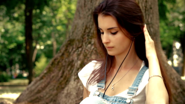 beautiful young lady with headphones in your ears, sitting near a tree and listens to music video