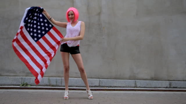 Beautiful young mixed race woman in pink wig with American flag at city street video