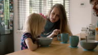 Beautiful young mother and her cute blond daughter are laughing happily at kitchen table. Slow mo video