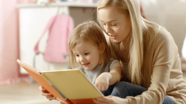 Beautiful Young Mother and Her Cute Little Daughter Read Children's Book Together. Children's Room is Pink and Full of Toys. video