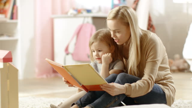 Beautiful Young Mother Reads to Her Cute Little Daughter from a Children's Book. Children's Room is Pink and Full of Toys. video