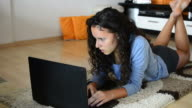 Beautiful young teen girl laying in living room with laptop video