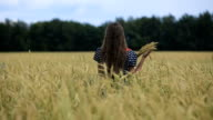 Beautiful young teen girl with ears of wheat in a wheat field video
