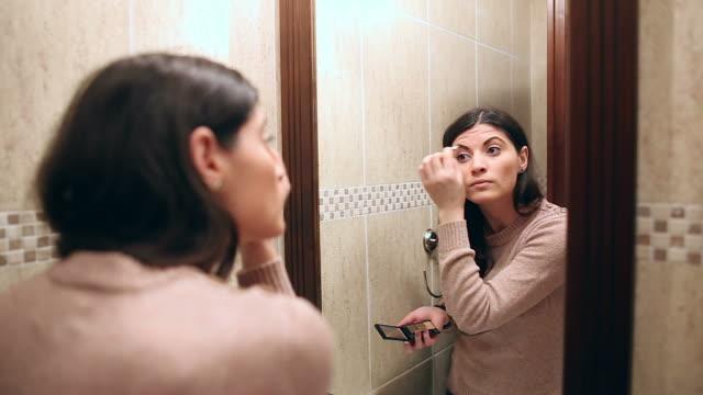 Beautiful young woman applying cosmetics. video