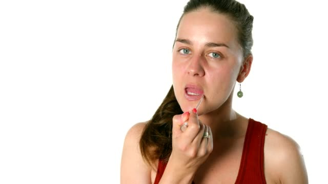 Beautiful young woman applying lipstick gloss doing her make up video