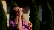 A beautiful young woman blowing bubbles video