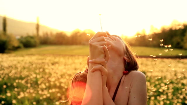 Beautiful Young Woman Blowing Dandelion Laughing on Summer Field HD video