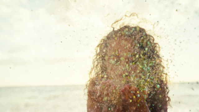 Beautiful young woman blowing glitter confetti in slow motion on the beach at sunset video