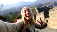 Beautiful young woman capturing selfie on Great Wall-China video