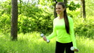 Beautiful young woman doing exercise whith dumbbell forest summer day video