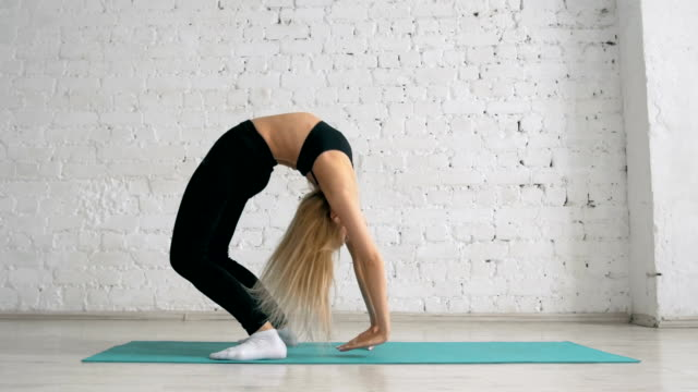 Beautiful Young Woman Doing Yoga Exercise, Stretching, Standing In Bridge Pose video