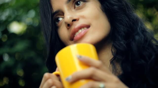 Beautiful young woman enjoying coffee in fresh air. video