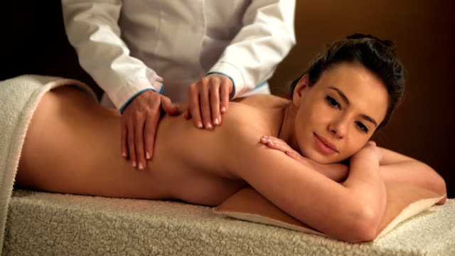 Beautiful young woman enjoys massage in a luxury spa resort video