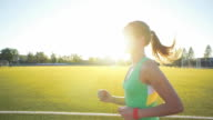 Beautiful young woman exercise jogging and running on athletic track on stadium at sunrise. Cinematic style video video