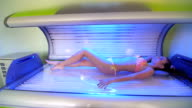 Beautiful young woman have tanning skin treatment in modern solarium video