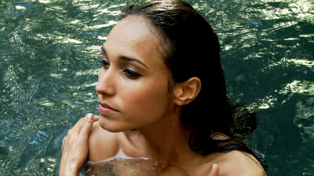 Beautiful young woman in a natural pool video