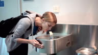 Beautiful young woman in airport terminal. Drinking water from drinking fountain. Tired and thirsty video