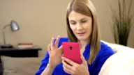 Beautiful young woman in blue t-shirt with smartphone sitting on sofa. Browsing Internet smiling video