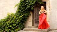 Beautiful young woman in fashion red dress posing video