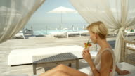 SLOW MOTION: Beautiful young woman in high class exotic resort sipping cocktails video