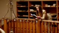 Beautiful young woman in suit and glasses spending time in the old vintage library reading book video