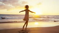 Beautiful young woman in sundress spinning on the beach at sunset in slow motion video