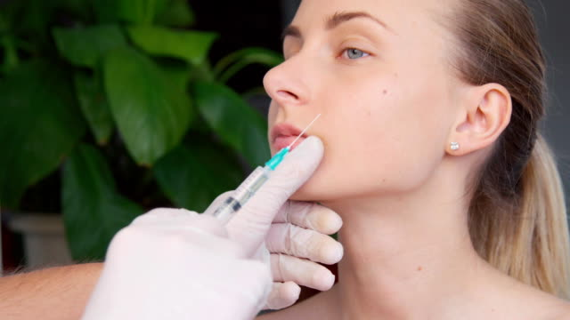 Beautiful young woman is getting botox injection video