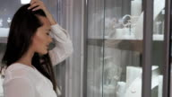 Beautiful young woman looking in a shop window with watches and luxury juwellery in shopping mallt video