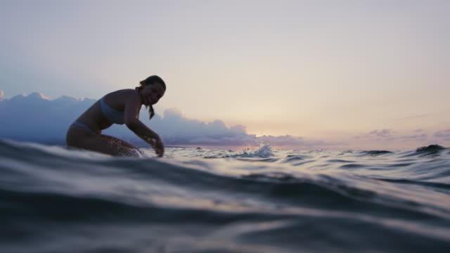 Beautiful young woman paddling surfboard in bikini video