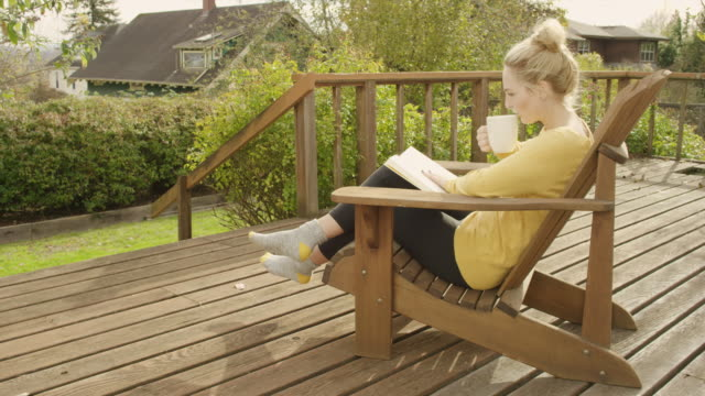 Beautiful young woman reading a book and drinking coffee outdoors video