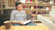 Beautiful young woman reading a book in a coffee shop. video