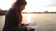 Beautiful young woman reading a book on the lake edge video