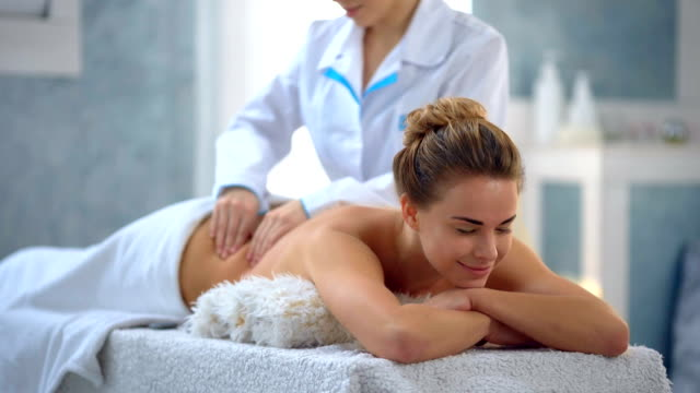 Beautiful young woman receiving a massage in a spa video